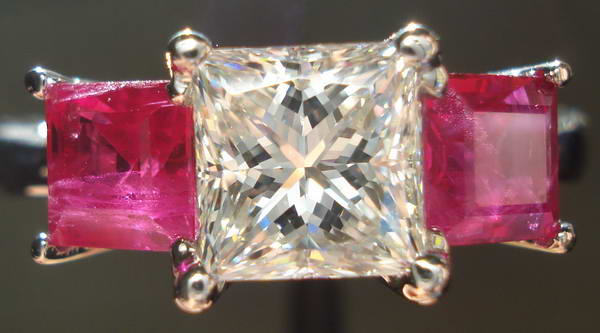 three stone diamond ring with white center diamond and ruby side stones